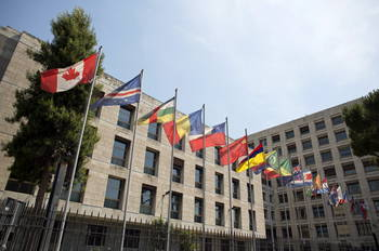Row of country flags in front of a building.